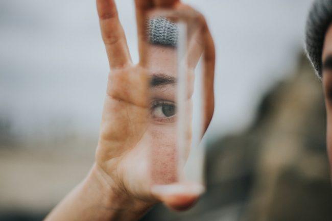 EXIT-Deutschland, Hand hält Spiegelstück. Darin spiegelt sich ein Auge.